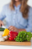 Chopping board with vegetables on a table — Stock Photo