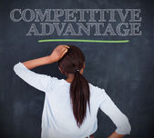 Woman looking at the word competitive advantage — Stock Photo