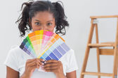 Happy woman showing colour charts — Stock Photo