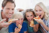 Smiling family eating pizza — Stock Photo