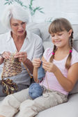 Little girl and her granddaughter knitting together — Stock Photo