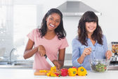 Happy friends preparing a salad together — Stock Photo