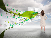 Creative businesswoman drawing on a paper next to paint splash — Stock fotografie
