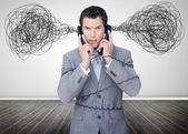 Overworked businessman holding two telephones — Photo
