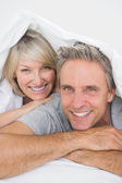 Couple smiling under the covers at the camera — Stock Photo