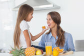 Little girl giving an orange segment to her mother — Stock Photo