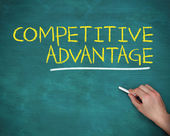 Hand holding a chalk and writing competitive advantage — Stock Photo