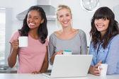 Heureux amis buvant café avec ordinateur portable — Photo