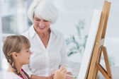 Grandmother and cute granddaughter painting together — Stock Photo