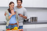Delighted couple clinking their glasses of red wine — Foto Stock