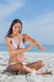 Happy woman sitting on beach applying sunscreen — Stock Photo