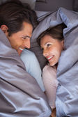 Lovely couple having fun wrapped in their blanket — Stock Photo