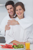 Man embracing his wife in the kitchen — Stock Photo