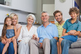 Extended family sitting on couch in living room — Stock Photo