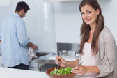 Woman mixing a salad in the kitchen — Stock Photo