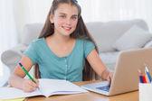 Smiling girl doing her homework — Stock Photo