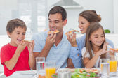Happy family eating pizza slices — Stock Photo