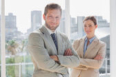 Smiling business partners with arms crossed — Stock Photo