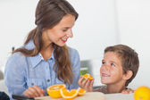 Little boy eating orange segments — Stock Photo