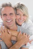 Hugging couple smiling at camera — Stock Photo