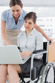 Businesswoman looking at co workers laptop who is sitting in whe — Stock Photo