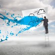Businessman standing on a ladder with blue paint splash — Stock Photo