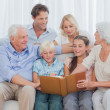 Extended cheerful family looking at a photo album — Stock Photo