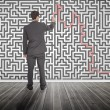 Businessman tracing a red line on a maze — Stock Photo