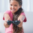 Smiling little girl playing video game on sofa — Stock Photo