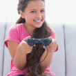 Little girl playing video game on sofa — Stock Photo