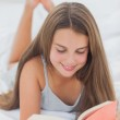 Smiling girl reading a book — Stock Photo #28051399