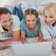 Foto Stock: Happy parents and daughter using a laptop