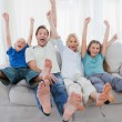 Family sitting on a couch and raising arms — Stock fotografie