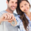 Man and wife presenting a key with a house keychain — Stock Photo