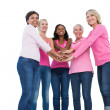 Cheerful women wearing breast cancer ribbons with hands together — Stock Photo #28052573