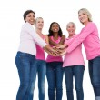 Cheerful women wearing breast cancer ribbons with hands together — Stock Photo