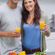 Delighted couple holding glass of orange juice — Stock Photo