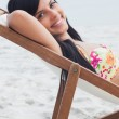 Beautiful woman resting on deck chair — Stock Photo