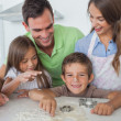 Brother with flour on the nose baking with his family — Stock Photo