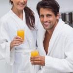 Lovely couple wearing bathrobes and holding glass of orange juic — Stock Photo