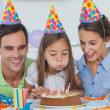 Little girl blowing out her candles — Stock Photo