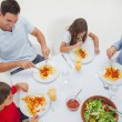 Overview of a family eating pasta with sauce and salad — Stock Photo