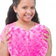 Little girl holding cushion in the shape of a heart — 图库照片