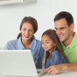 Family using a laptop on the kitchen table — Stock Photo #28053949