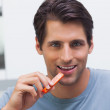 Handsome man eating a slice of bell pepper — Stock Photo #28053951