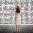 Puzzled businesswomlooking at maze — Stock Photo #28054035