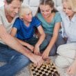 Portrait of a cheerful family playing chess — Stock Photo