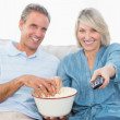Couple watching tv and eating popcorn on the couch — Stock Photo