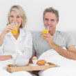 Couple having orange juice at breakfast in bed — Stock Photo