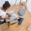 Stock Photo: Young housemates unpacking boxes in new home